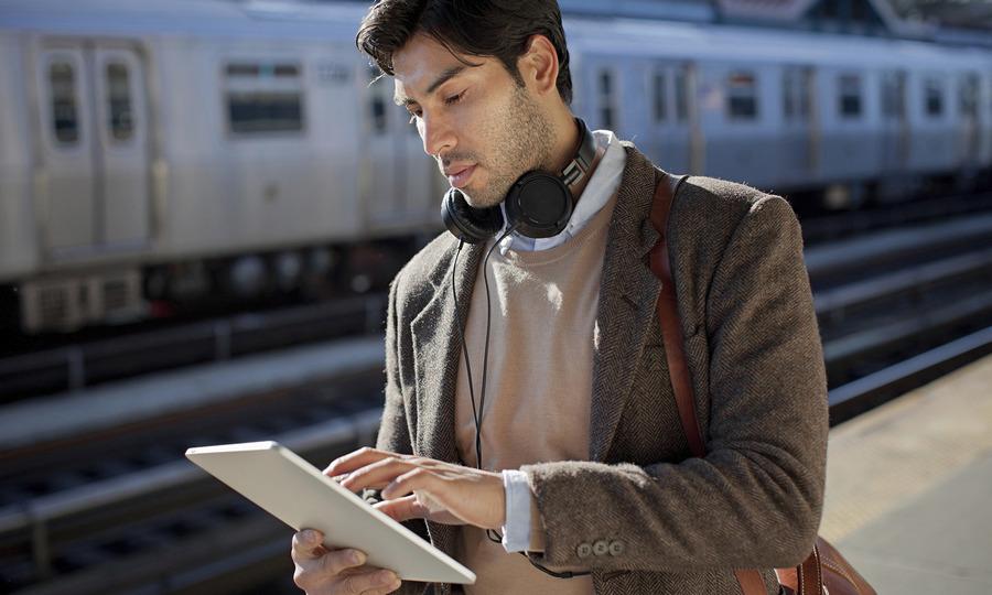 Man using tablet computer at station